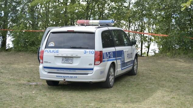 Une voiture de police devant la rive.