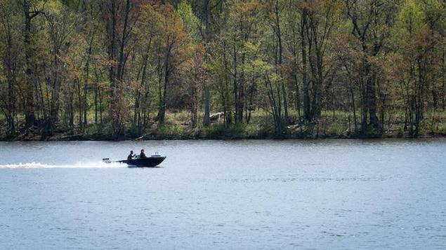 Deux personnes se trouvent à bord d'un bateau par beau temps.
