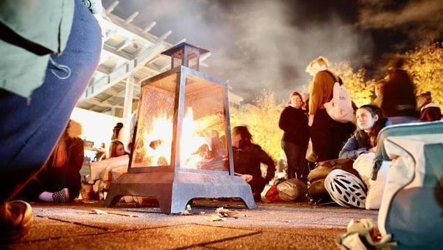 Des gens sont réunis autour d'un feu en ville le soir dans le cadre de la Nuit des sans-abris