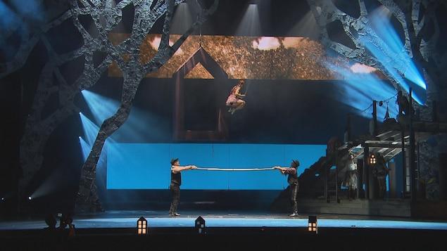 Femme qui saute avec un cerceau et deux cowboys qui tiennent une bar.
