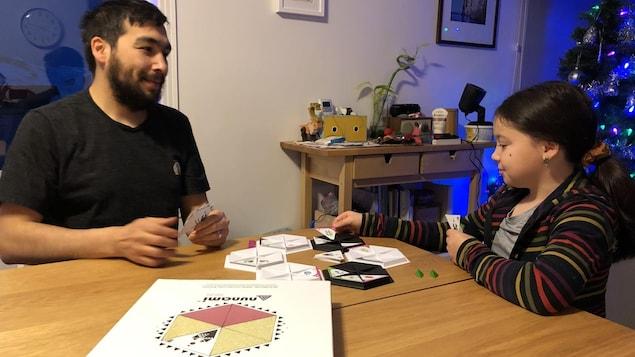 Un père et sa fille jouent à un jeu de société dans le salon.