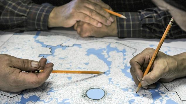 Des mains pointent avec des crayons certains endroits sur une carte géographique.