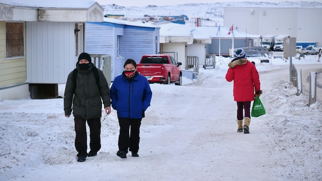 Des passants masqués dans une rue enneigée d'Iqaluit.