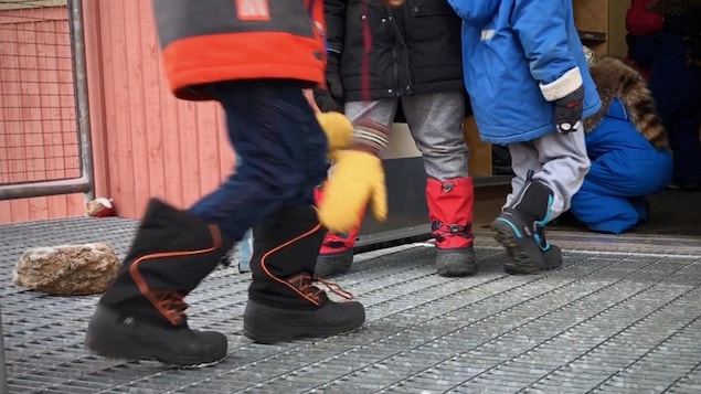 Des enfants habillés pour l'hiver entrent dans une école.