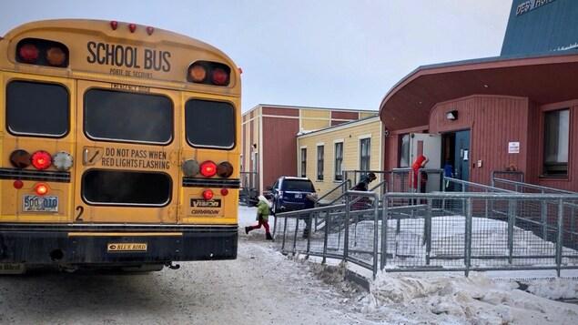 Un autobus scolaire dépose des enfants devant une école.