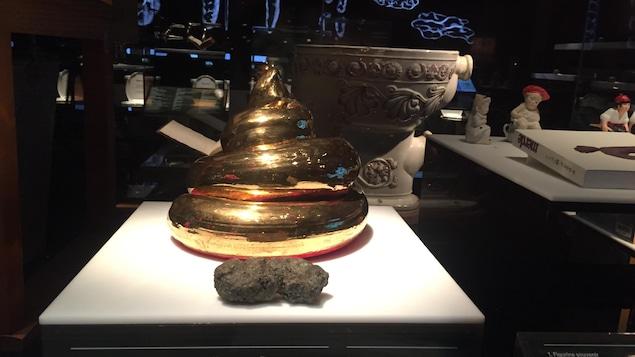 Une sculpture en forme de caca, de couleur or.
