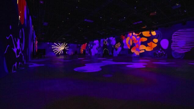 Une grande salle sur les murs de laquelle sont projetés des motifs de formes et de couleurs diverses.