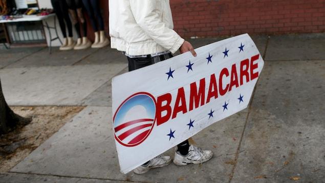 Une personne tient une affiche en forme de flèche sur laquelle il est écrit «Obamacare».