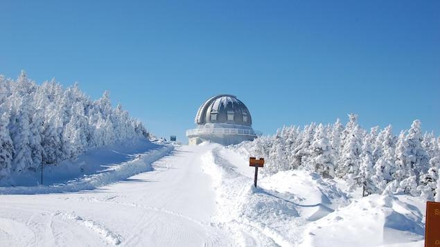 Un chemin mène vers l'Astrolab du Mont-Mégantic, qui est de forme sphérique. L'image a été captée alors que le chemin et les arbres sont enneigés.