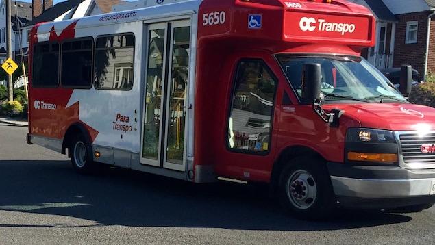 Un véhicule pour le transport adapté est stationné dans une rue résidentielle.