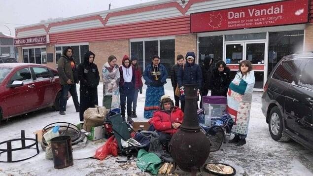 Des jeunes se tiennent autour d'un feu de camp devant le bureau du député à Winnipeg.