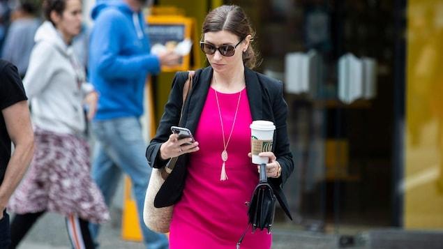 Une femme portant des lunettes de soleil et une robe marche dans la rue en regardant son cellulaire alors qu'elle porte un gobelet de café dans l'autre main.