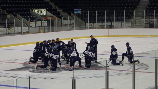 Des joueurs de hockey à genoux au centre de la patinoire, écoutant leur entraîneur.