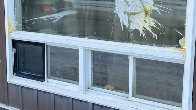 La vitre d'un bâtiment avec un oeuf écrasé dessus.