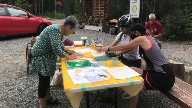 Trois femmes pratiquent le pochoir sur une table installée à l'accueil de la forêt récréative.
