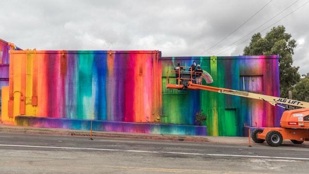 Des personnes dans une nacelle en train de peindre l'extérieur d'un édifice.