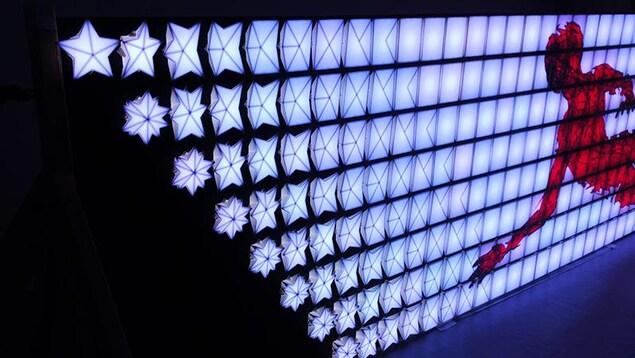 L'oeuvre numérique de Jean-Ambroise Vesac est faite de structures lumineuses en forme de carrés et d'étoiles.