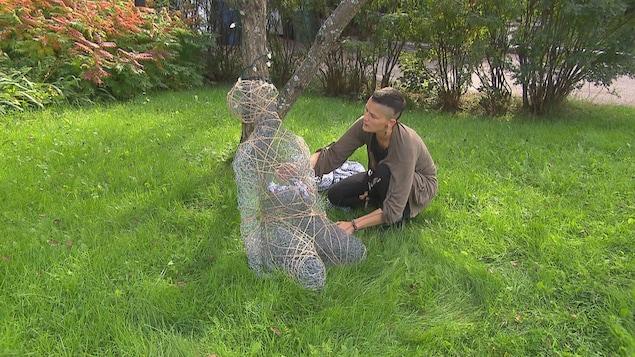 Une femme replace une sculpture.