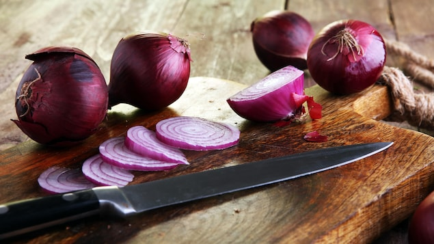 Des oignons rouges et un couteau sur une planche à découper.