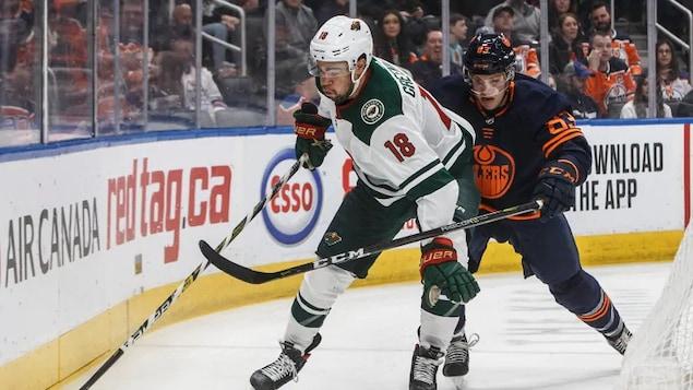 Jordan Greenway et Matt Benning sont sur la glace et luttent pour contrôler la rondelle.