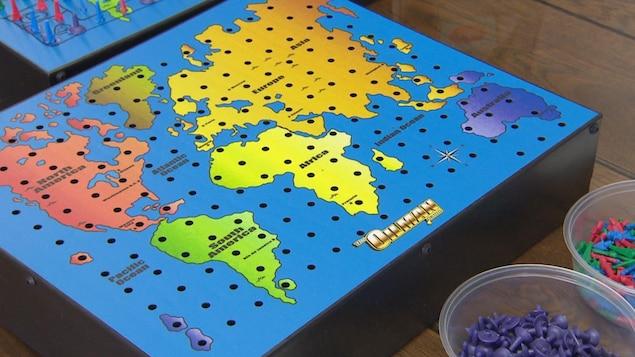 Un plateau de jeu de société. On y voit une carte du monde avec les continents de différentes couleurs. La carte est recouverte de trous.