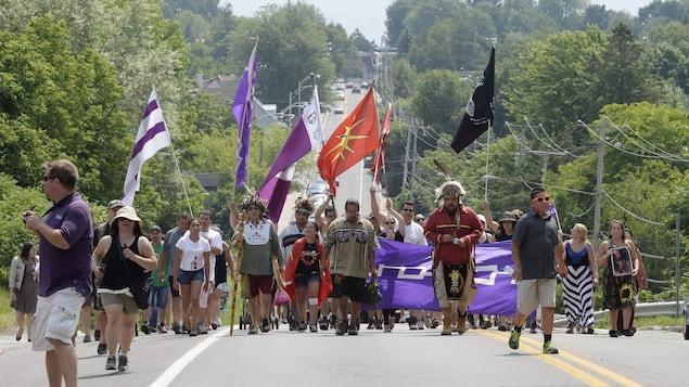 Des Mohawks de Kanesatake marchent dans une rue en brandissant des drapeaux.
