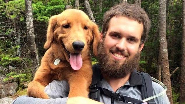 Olivier Bruneau tient son chien sur son épaule.