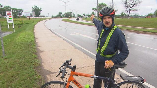 Un homme tient son vélo.