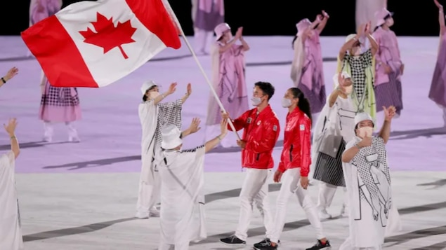 Canadian flag-bearers Nathan Hirayama, left, and Miranda Ayim, right, lead Team Canada into the opening ceremony of the 2020 Tokyo Olympic Games at Olympic Stadium on Friday in Tokyo, Japan.