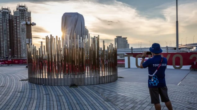 A member of Tokyo 2020 staff takes pictures of an Olympic cauldron at Yume-no-Ohashi Bridge on July 21, 2021 in Tokyo, Japan. The opening ceremony of the Games begins on Friday.