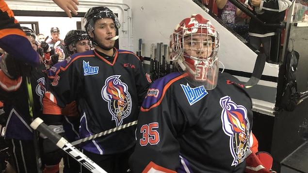 Des joueurs de hockey sortent du vestiaire pour entrer sur la glace.