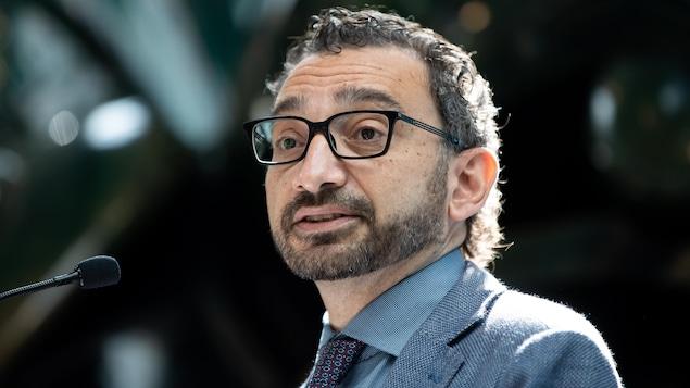 Omar Alghabra porte des lunettes et parle dans un micro.