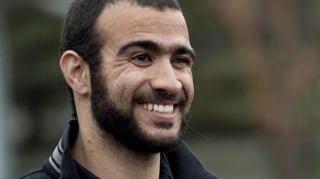 Omar Khadr, souriant, alors qu'il s'adressait aux médias à sa sortie de prison, le 7 mai 2015.