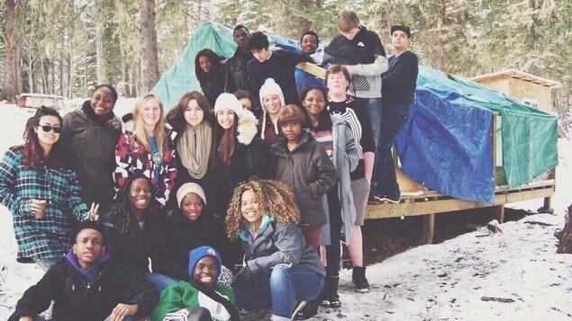 Un groupe d'adolescents pose pour une photo à l'extérieur, en hiver.