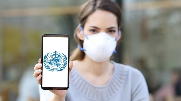 Une femme portant un masque montre un téléphone cellulaire sur lequel est affiché le logo de l'Organisation mondiale de la santé.