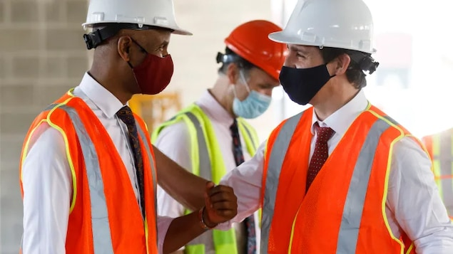 Prime Minister Justin Trudeau, right, greets Social Development Minister Ahmed Hussen as they tour an affordable housing complex under construction in Hamilton on July 20.