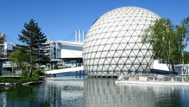 La sphère géante blanche de la Place de l'Ontario et la passerelle qui y mène au-dessus de l'eau.