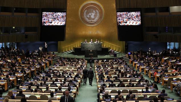 Le secrétaire général désigné de l'ONU, Antonio Guterres, du Portugal, descend le centre de l'allée au siège de l'ONU à New York.
