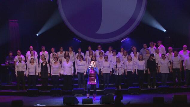 Une chanteuse chante devant une chorale sur une scène.