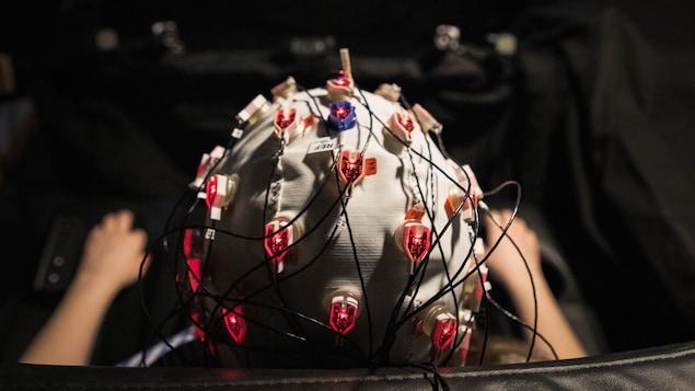 Une participante à l'étude porte un casque d'encéphalographie tout regardant un opéra.