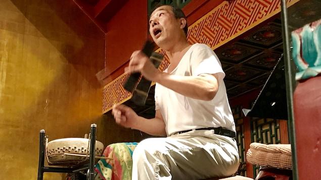 Un homme joue du tambour.