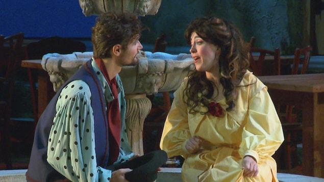 Deux chanteurs d'opéra, costumés et maquillés, pendant une scène, lors d'une représentation. Ils se regardent tendrement.