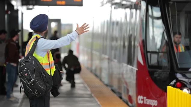 Un opérateur de train léger attend le train.