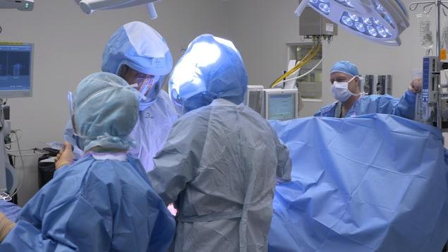 Une salle d'opération, médecin et personnel sont masqués, le patient est sous un grand drap bleu.