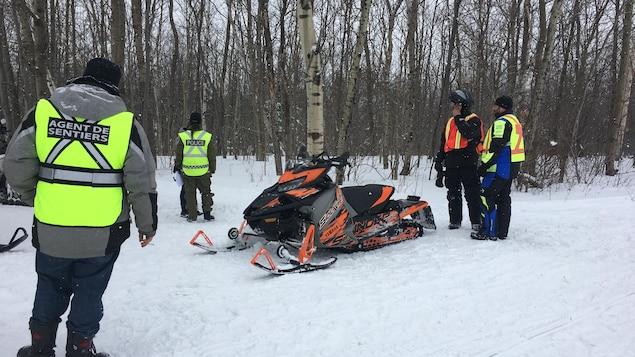 Des agents de sentiers et des agents de la SQ lors d'une opération de sensibilisation à la sécurité en motoneige à Donnacona