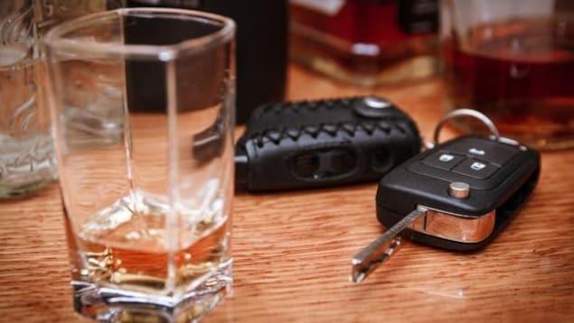 Des clés de voiture et un verre d'alcool.