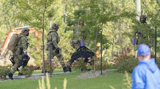 Des agents en tenue de camouflage transportent de l'équipement.
