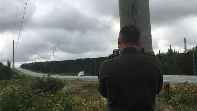 Un policier capte la vitesse des automobilistes avec un cinémomètre.
