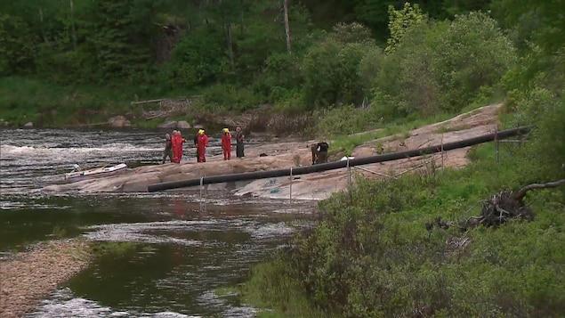 Des secouristes se tiennent sur l'une des rives de la rivière Malbaie. On aperçoit un canot pneumatique échoué sur des rochers.
