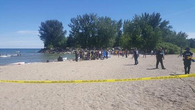 Un cordon de police et des personnes sur la plage.